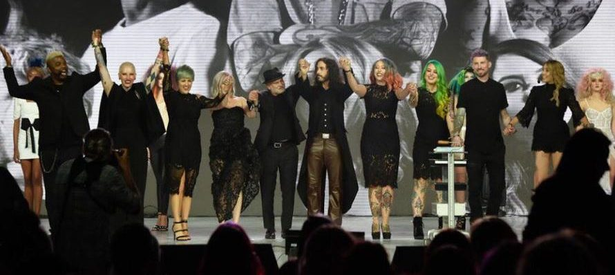 Ten people on stage holding hands in front of a crowd.